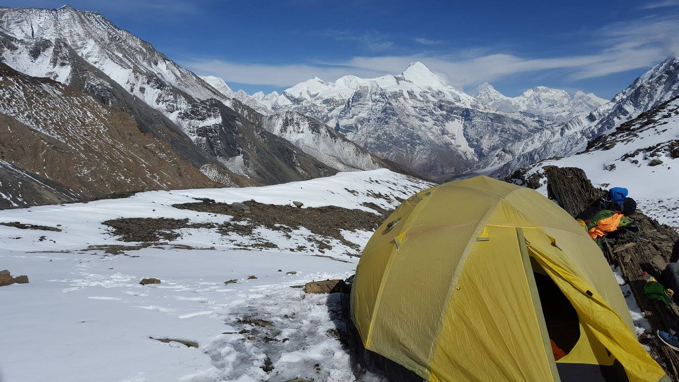 lots of himalaya mountain landscapes that are covered with snow, with a blue sky and a yellow tent with things on its sides