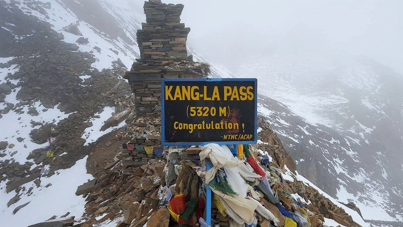 a mountain covered with snow and with a pile rock and flags in front of it is a signage saying