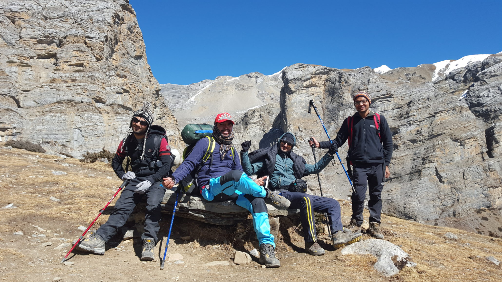 a group of 4 trekkers on a rock and behind them are himalayas mountains
