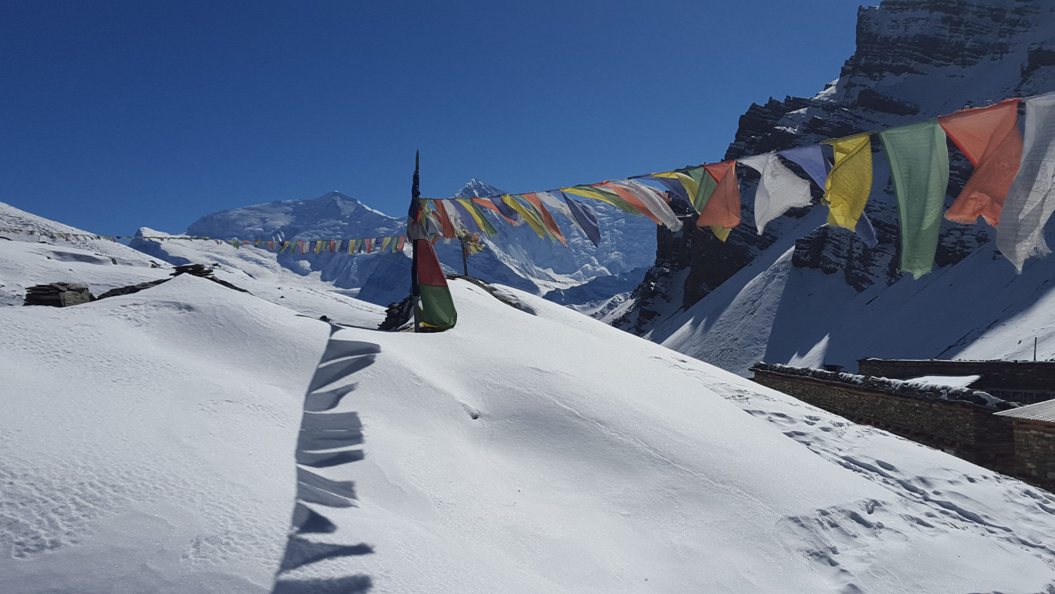 snow covered mountains with colorful prayer flags on a pole