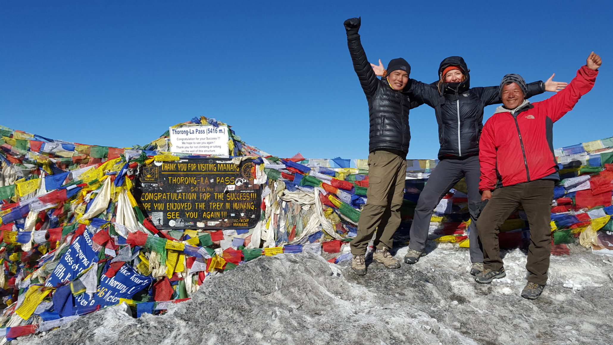 3 himalayan trekkers taking picture at the thorong-la pass