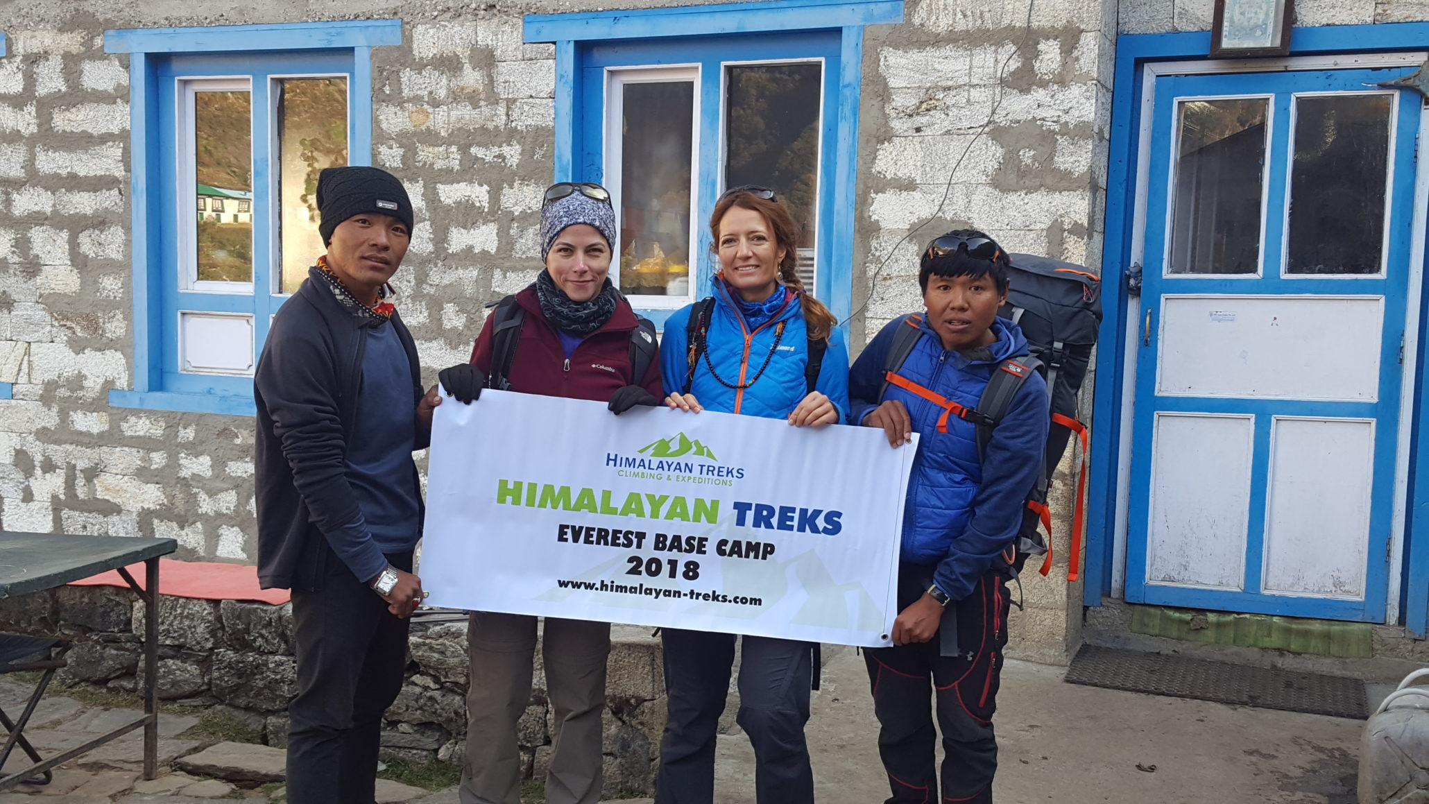 a signage with HIMALAYAN TREKS EVEREST BASE CAMP held by 4 trekkers