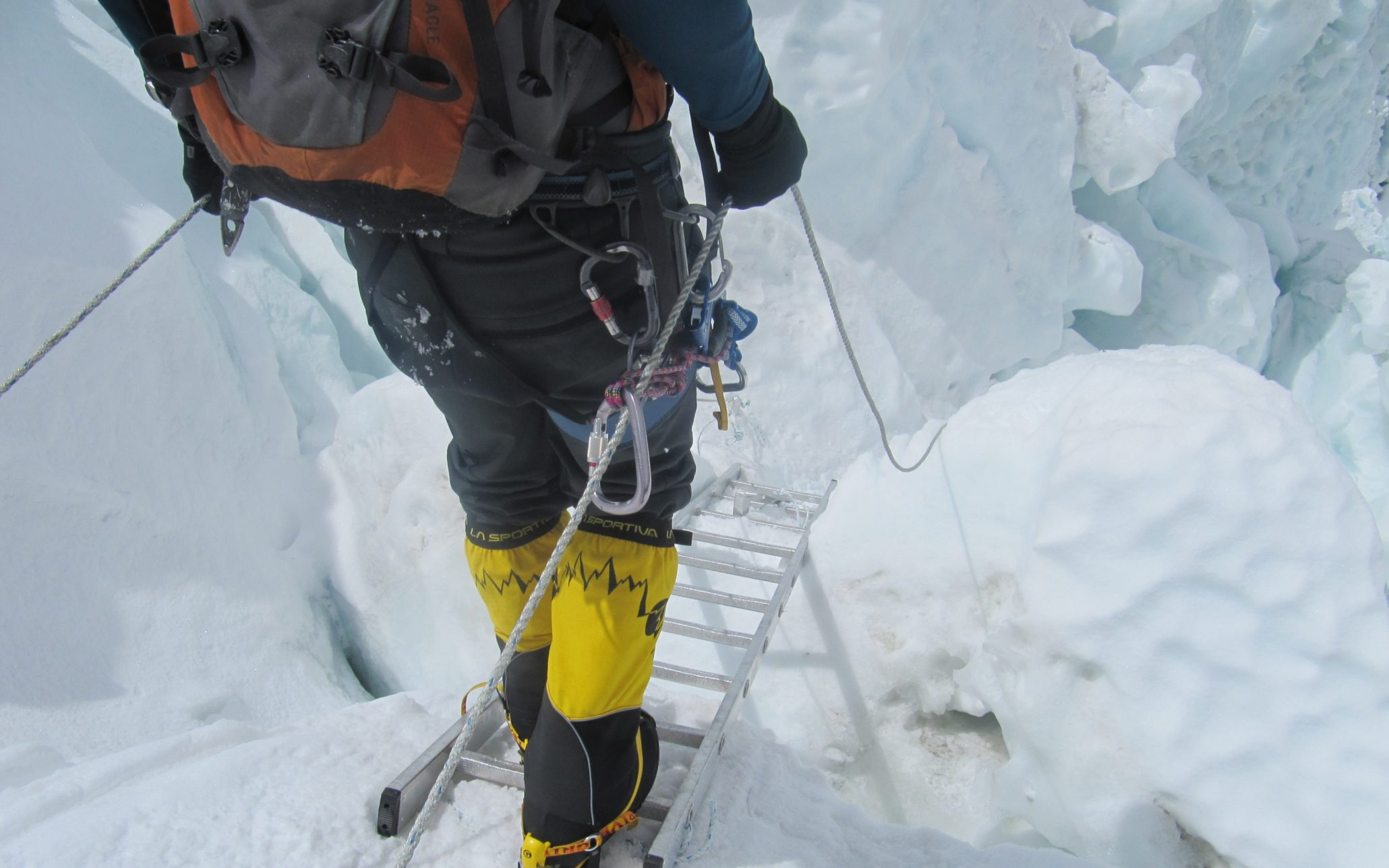 himalayan moutaineer crossing icefall with a ladder