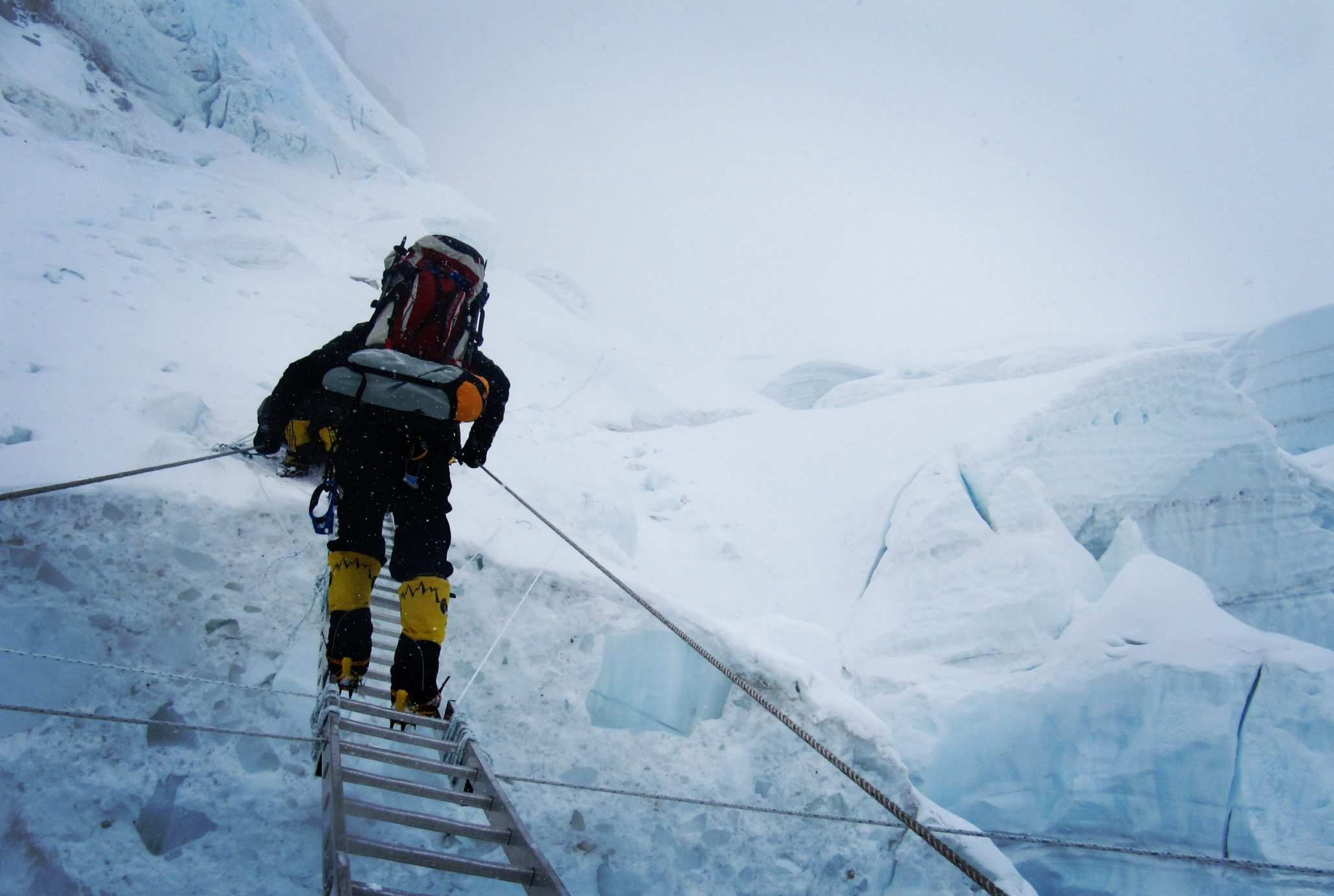 himalayan mountaineer climbing on the mountain covered with snow using a ladder