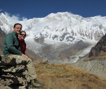 A couple posing for a picture of the view of the glacial mountain in Annapurna Sanctuary Trek.