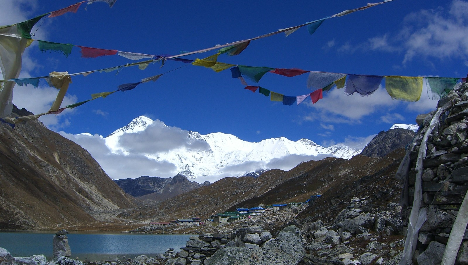 buntings hanged beside a pile of rocks and a view of Himalaya mountains from building structures
