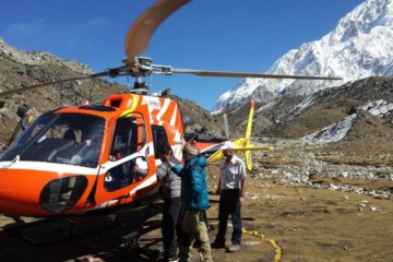 Three people entering a helicopter at the glacier part of the mountain in Everest Base Camp.