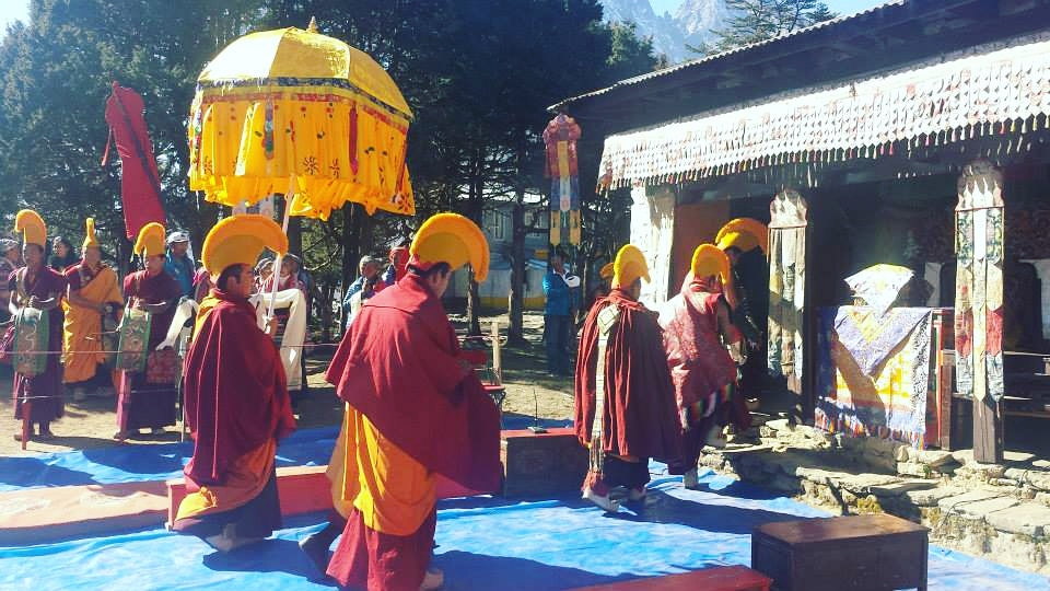 A group of monks wearing maroon yellow costume entering the monastery during the Mani Rimdu Festival in Tengboche.