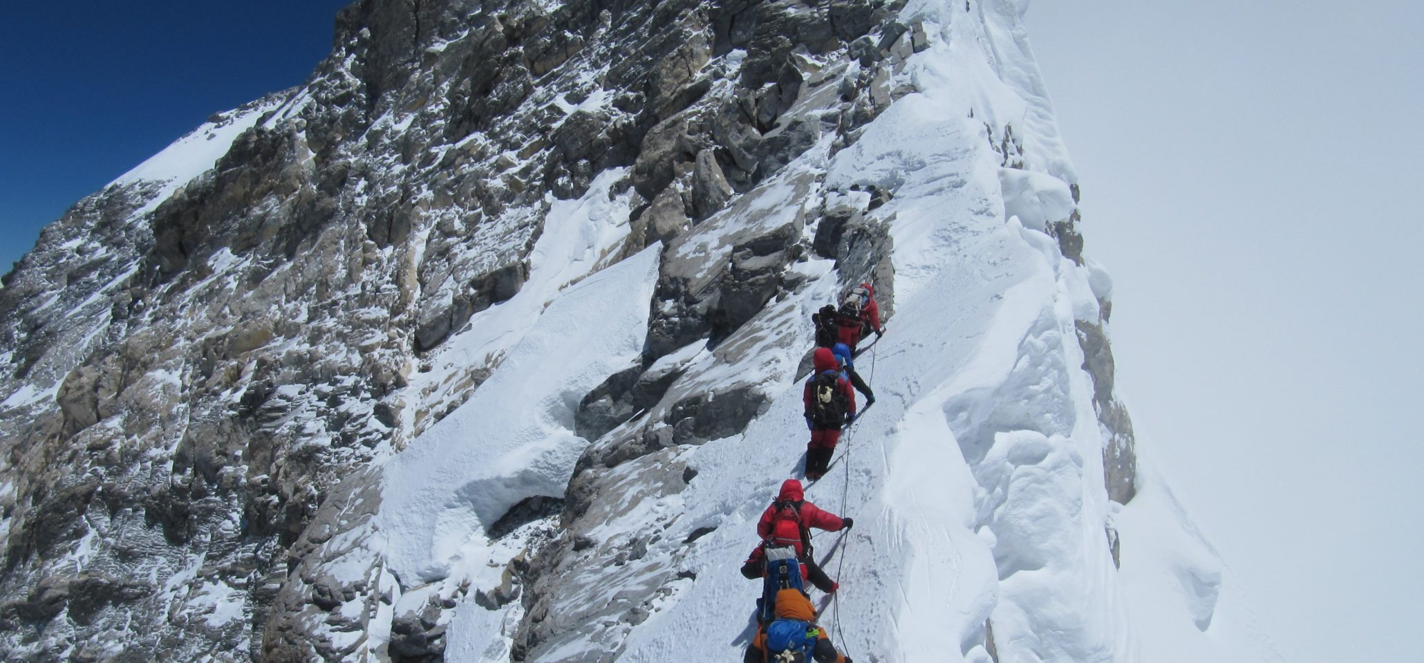 6 himalayan trekkers at the peak of the mt. everest