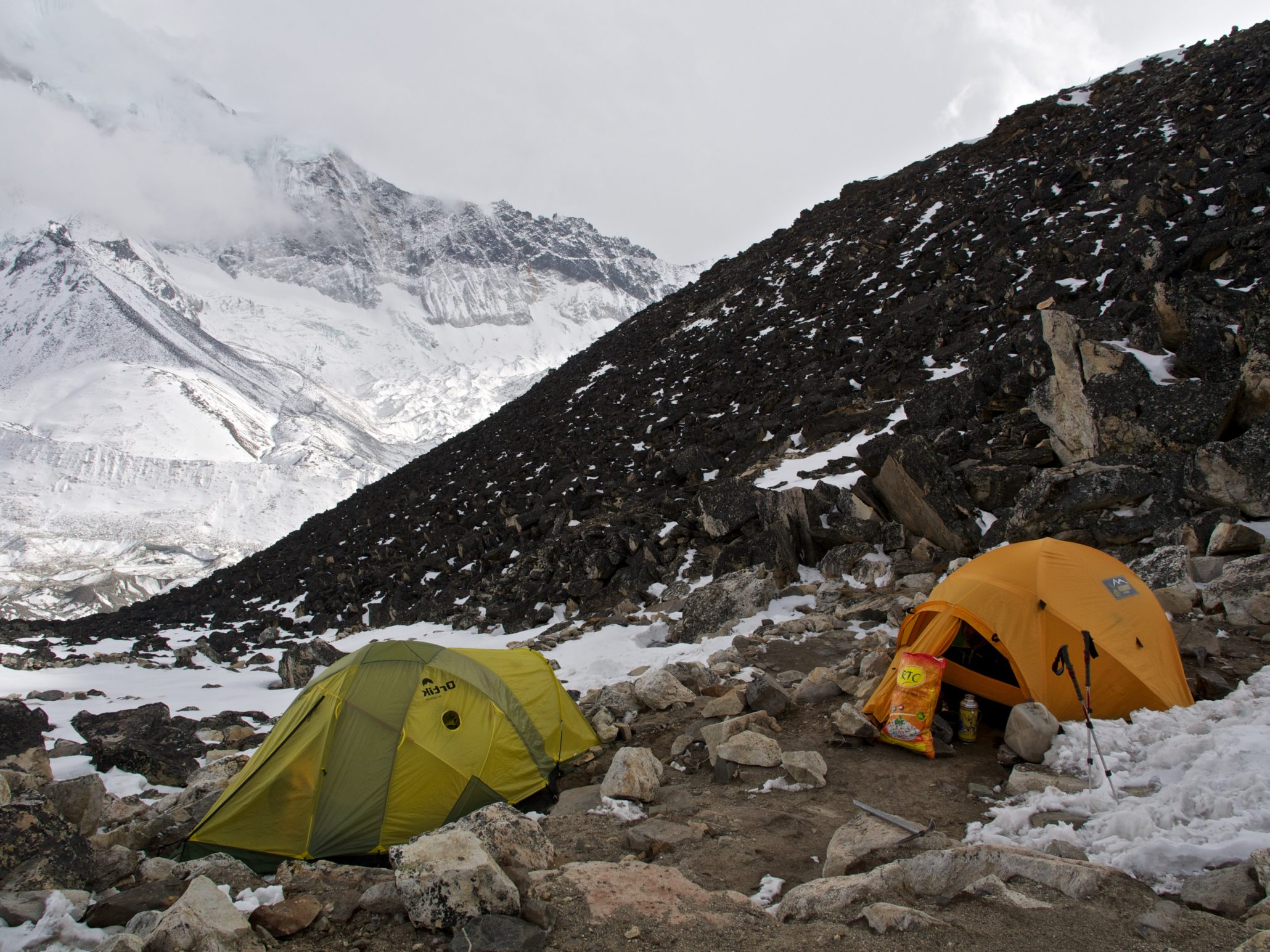 2 tents settled at the foot of rocky mountains