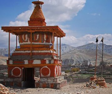 A temple with the view of the mountain and houses at the back of it in Shey Gompa (Upper Dolpo).