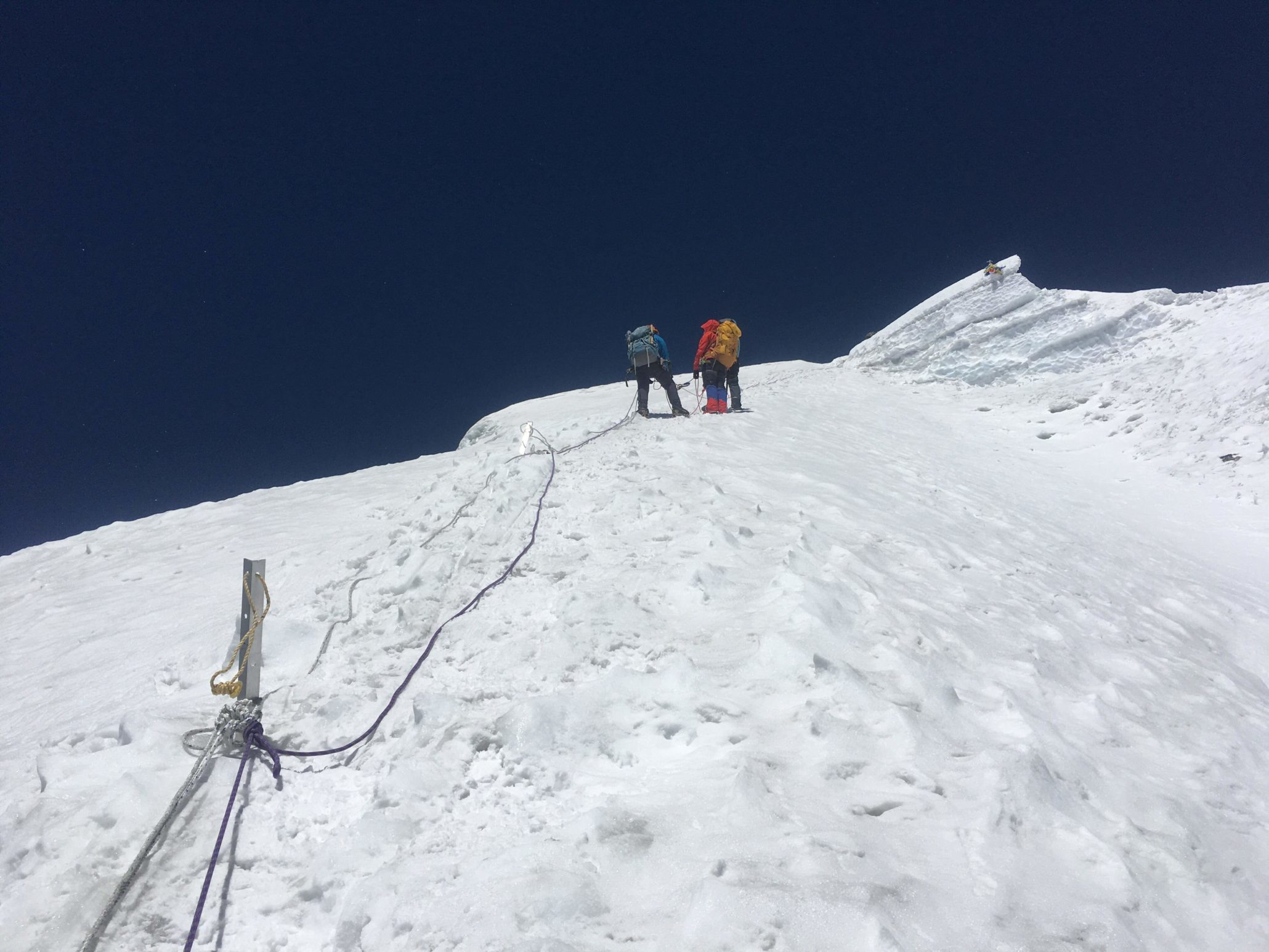 2 himalayan trekkers at the peak of mountain covered with snow