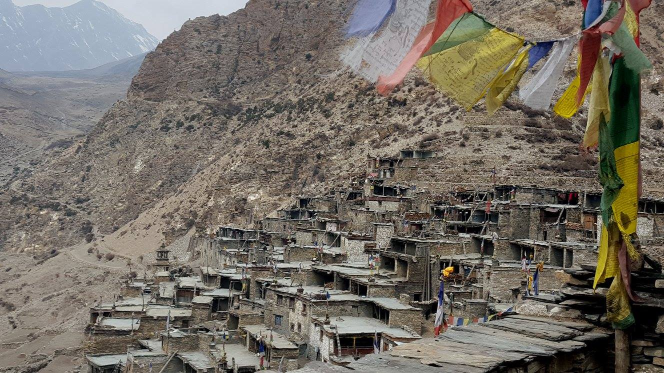 a mountain of Nepali villagers where their houses are attached to the mountain and to the other houses, there are flags attached to a pole