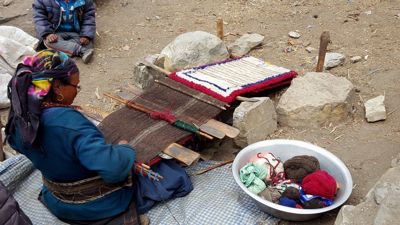 a weaving Nepali woman with a basin of threads on her right side