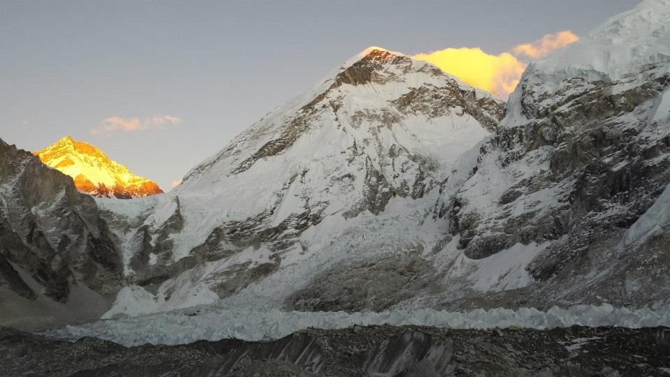 a view of a mountain covered with snow during sunrise