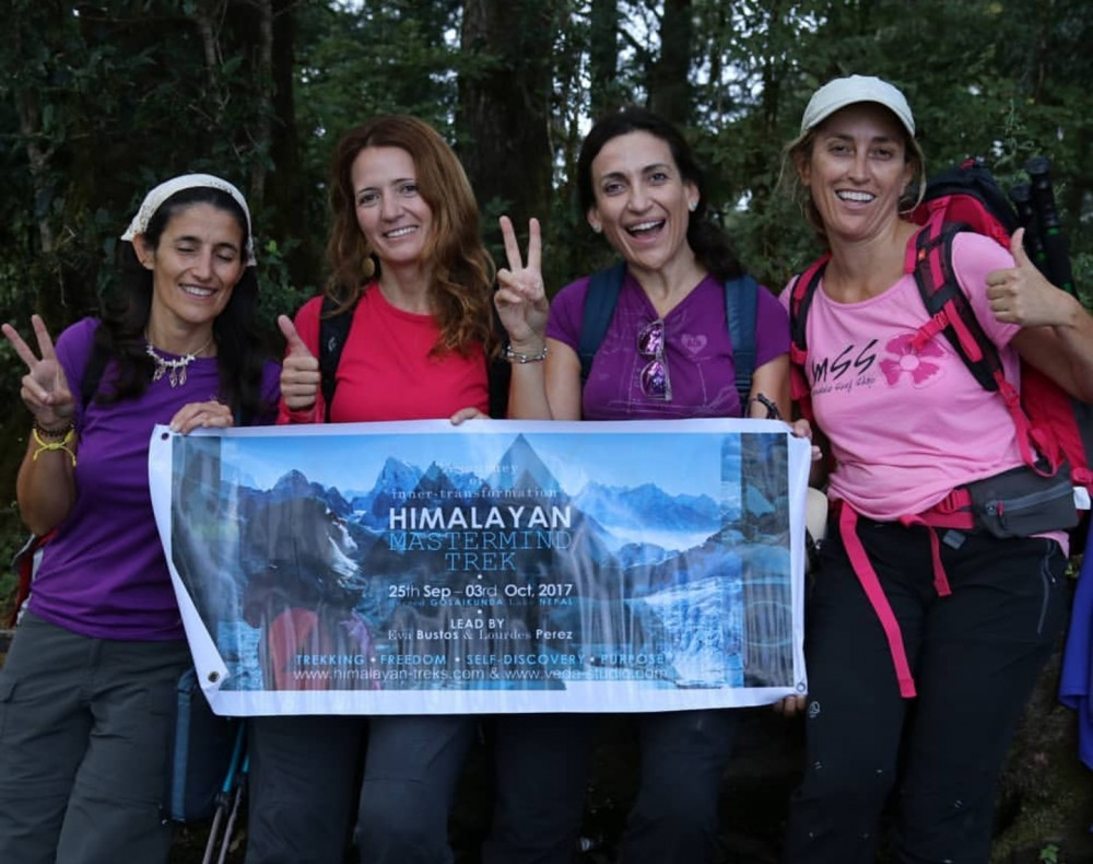 4 woman posing with trekking attire and holding a small tarpaulin of Himalayan Treks Ltd.