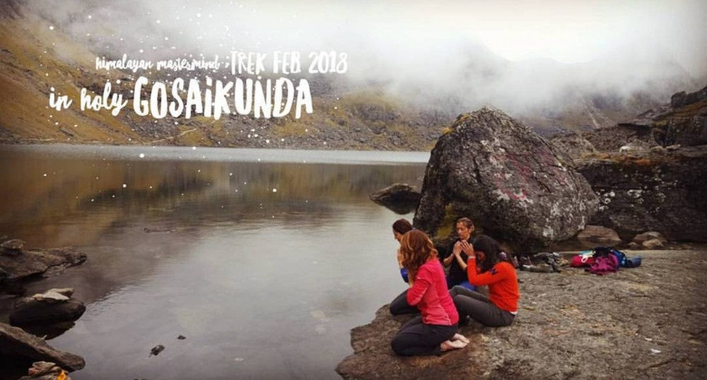 4 woman praying near a lake surrounded with mountains in Gosaikunda.