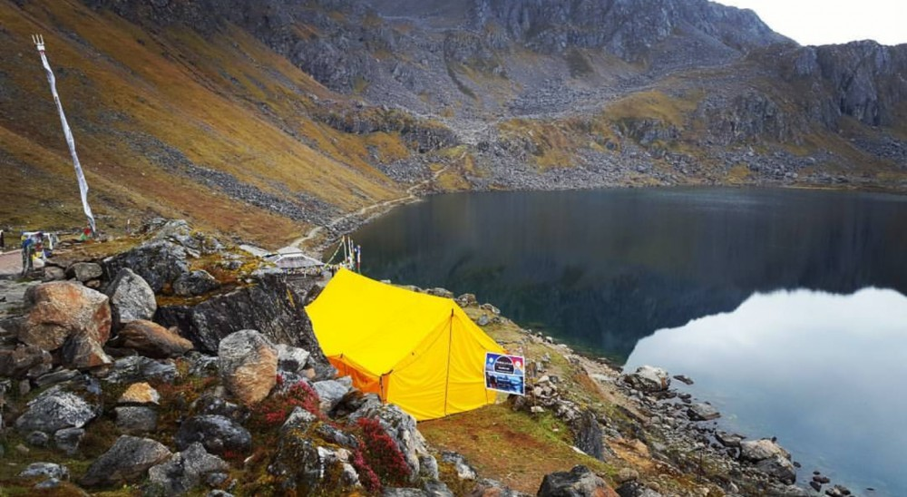 View of a yellow tent on top of a plateau with lake near it and surrounded with mountains.