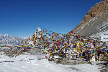 Prayer flags scattered in a cliffside of a mountain
