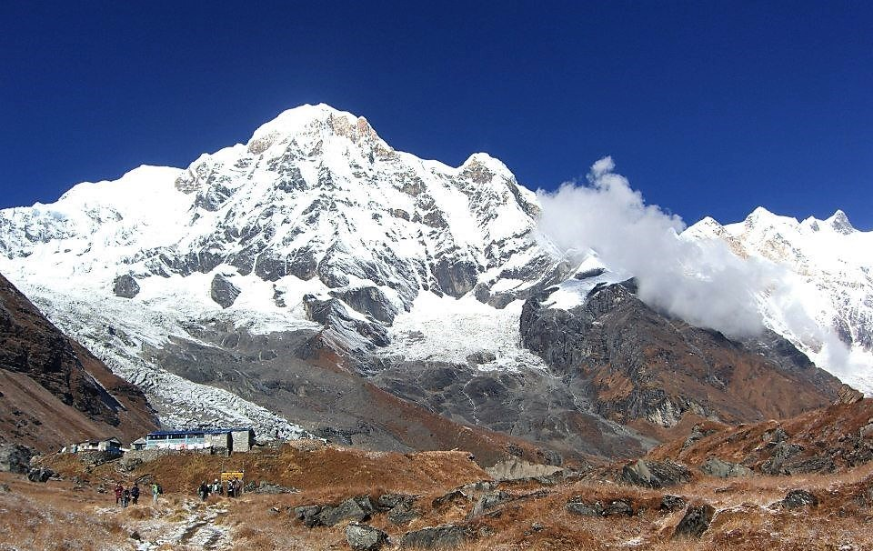 a himalaya mountain covered with snow and there are people at the foot of the mountain beside a building structure