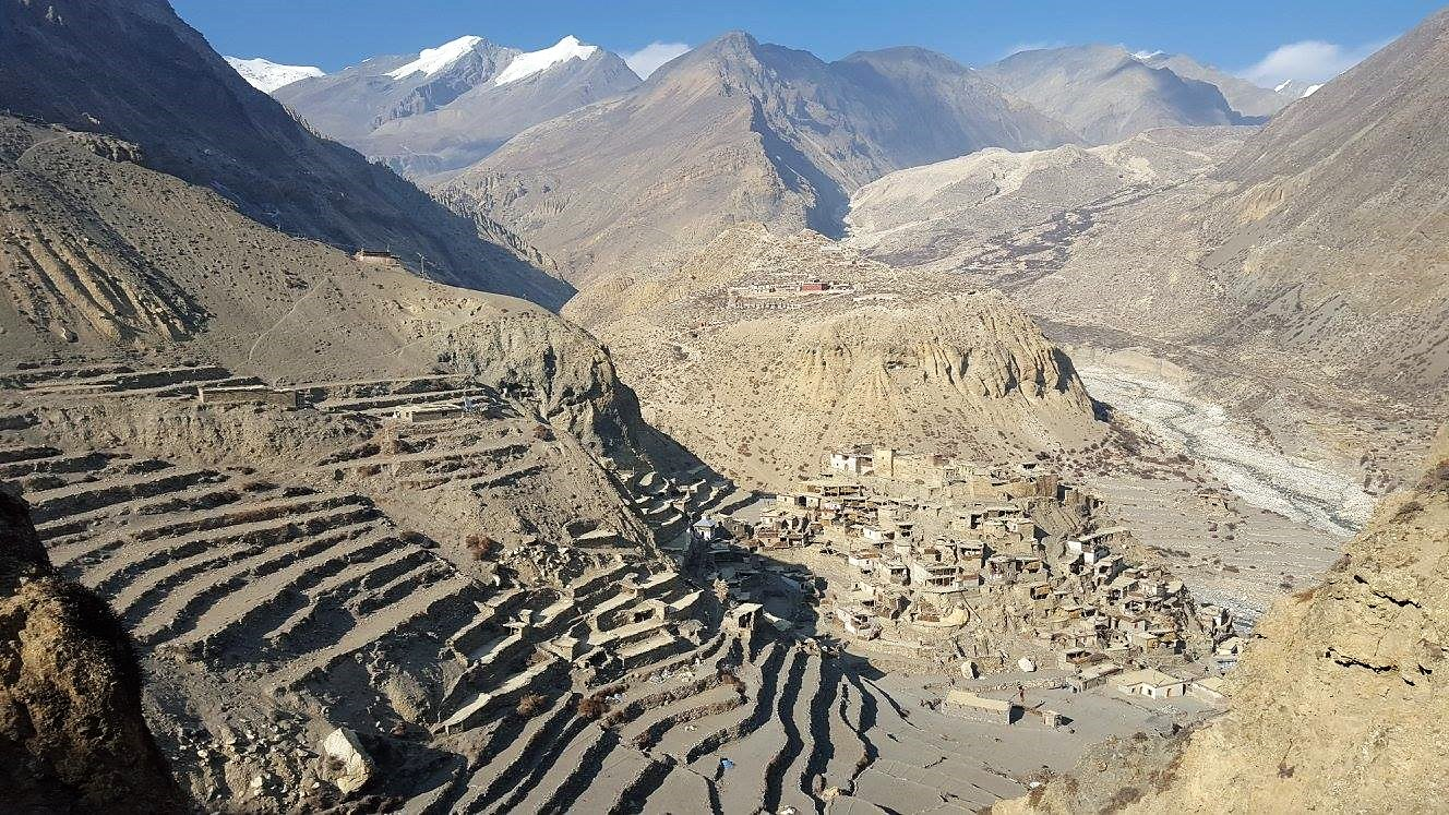 a barren mountain side of himalaya with a village at its foot, terraces landscapes