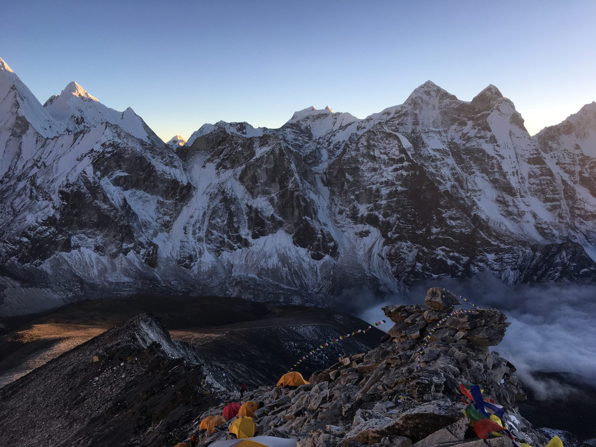 a group himalayan trekkers with their tent settled at the rocky mountain in himalaya