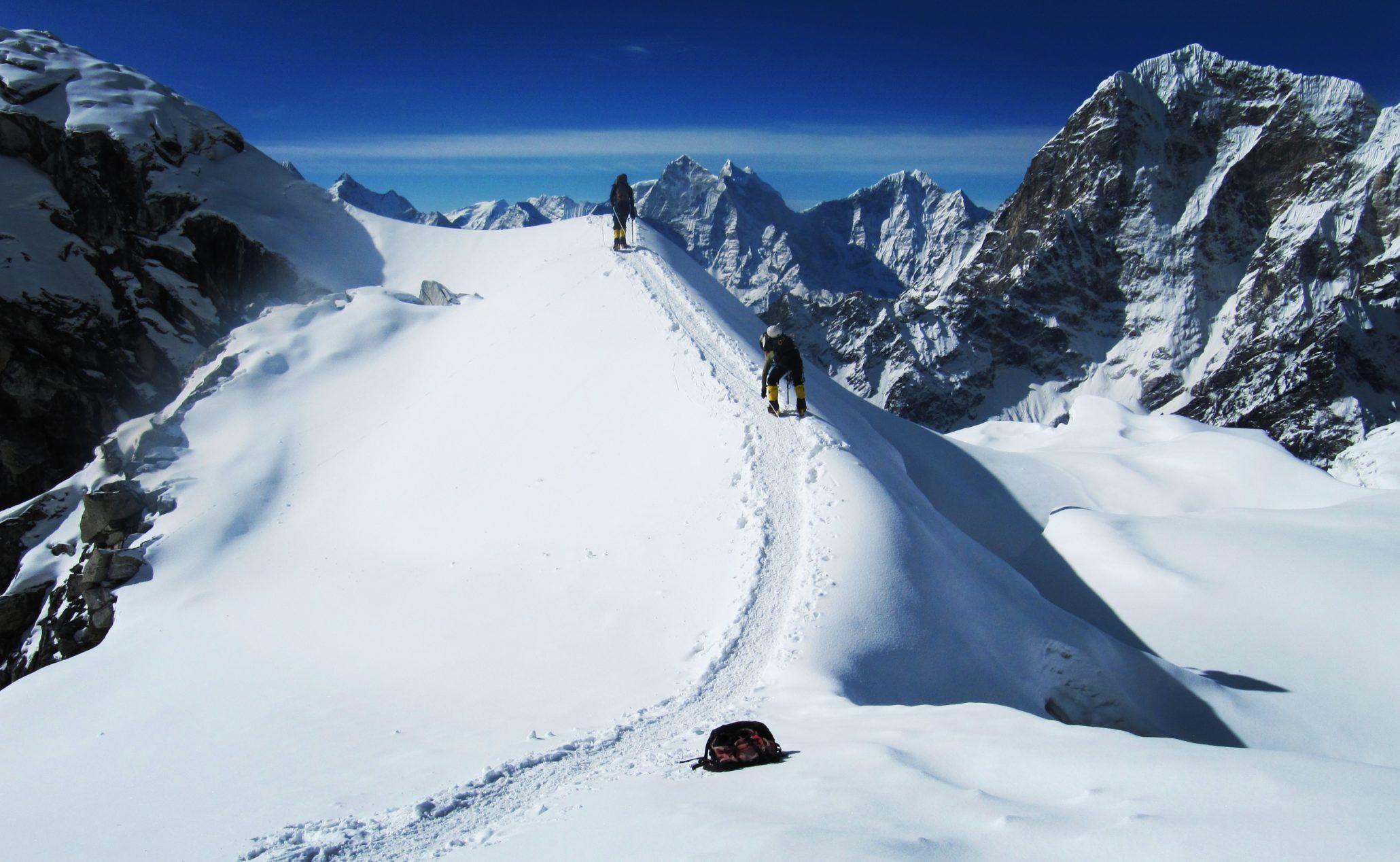 2 himalayan trekkers at the peak of lobuche in himalayas