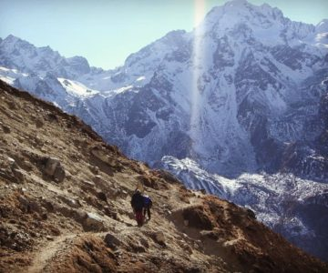 Two people trekking at the side of the mountain in Himalayas.