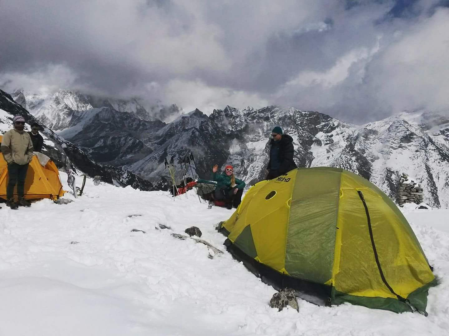 a group of himalayan trekkers with their tent at the top of snow-capped mountain