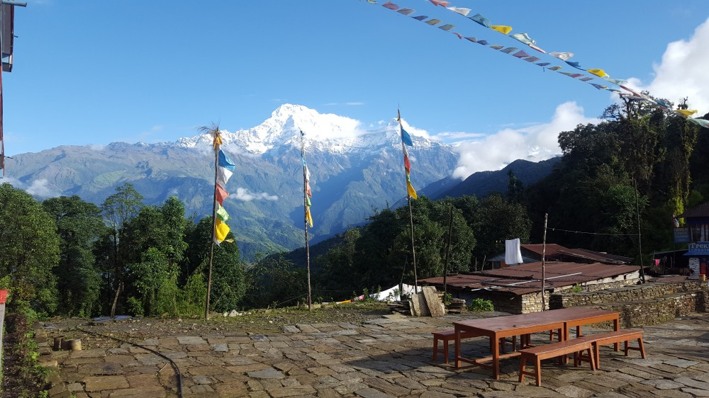 A view of the mountain from the houses in a village with a festival banners and poles in Mardi Himal Trek.