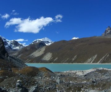 A view of a clear water valley and some glacier part of the mountain in Three Passes Trek.