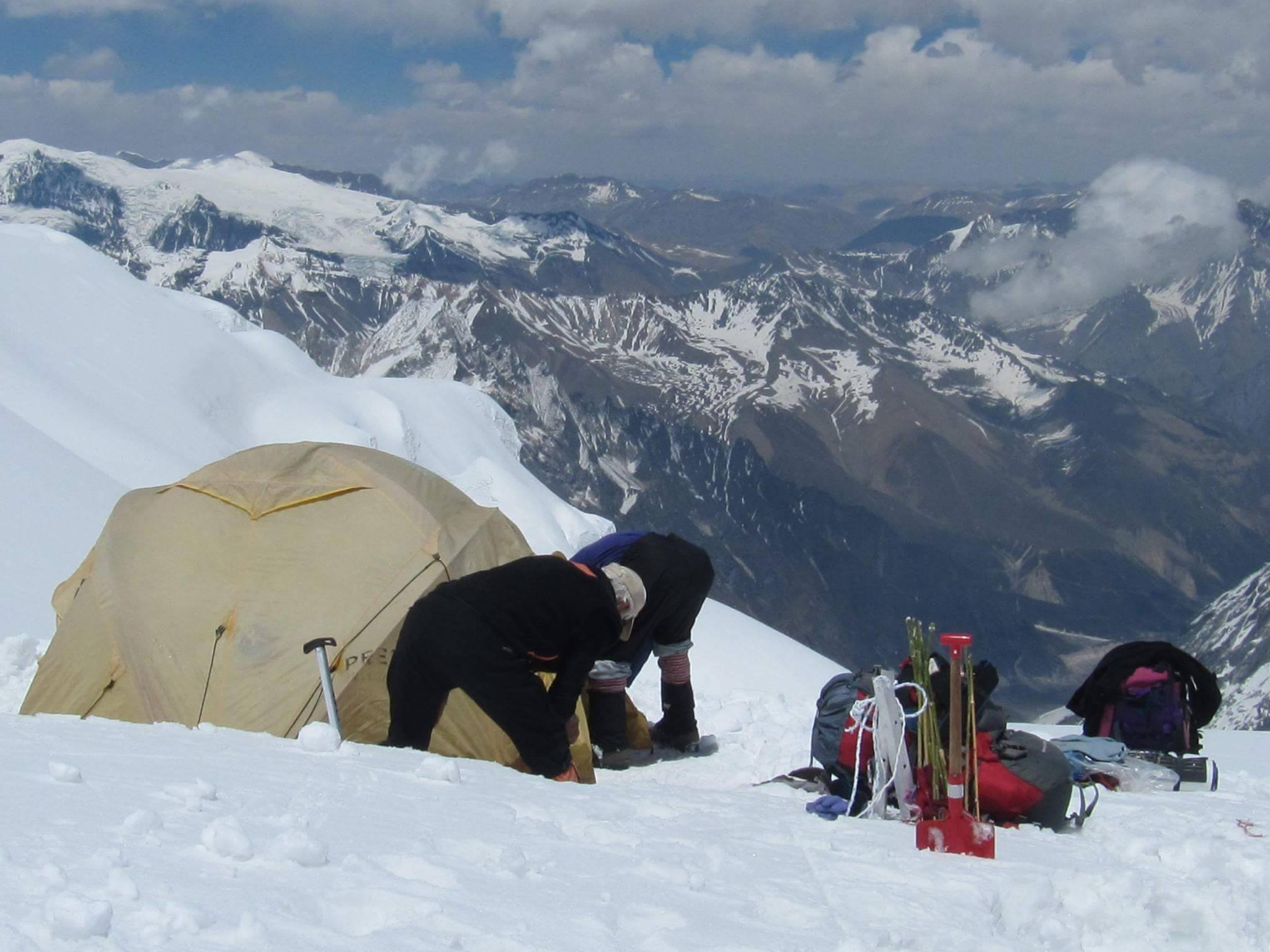 2 trekkers with a tent at the peak of himalayas mountain