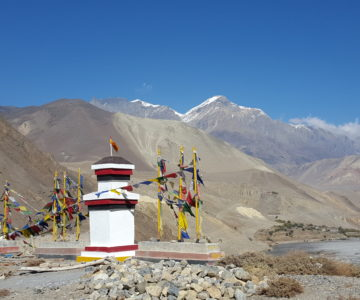 a picture of a shrine in Nepal with the Himalayan Mountains as the background