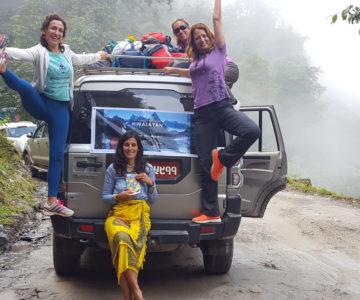 4 women riding a car towards the mountain