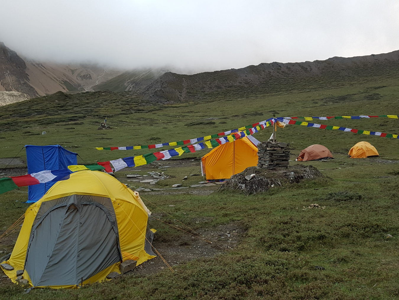 Base camp beside the colorful prayer flag pole at the foot of himalayas mountain