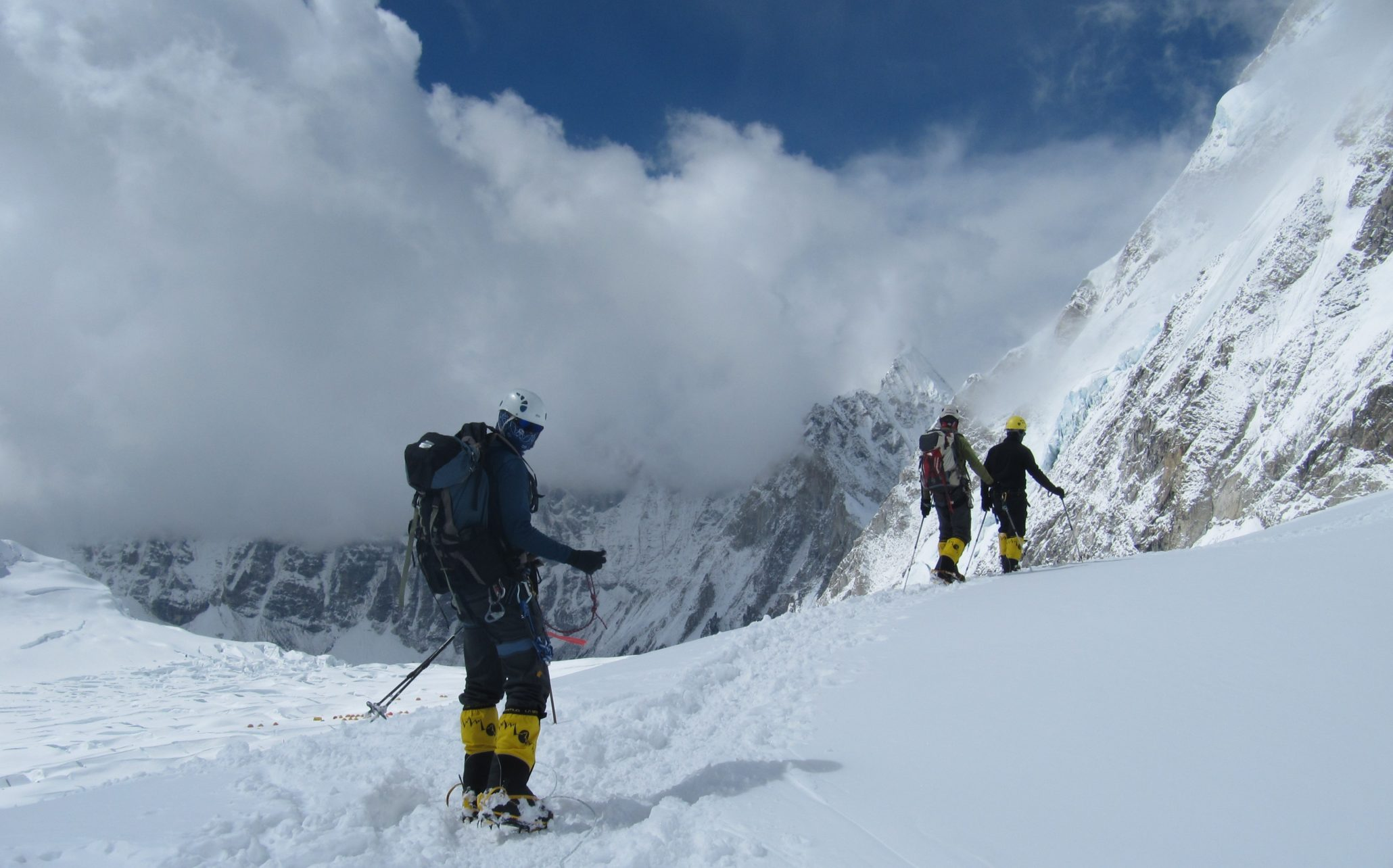 3 trekkers at the top of a mountain covered with snow