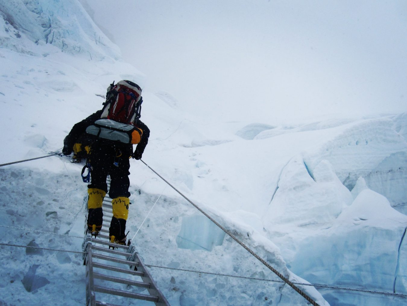 trekkers crossing icefall in himalayas mountains