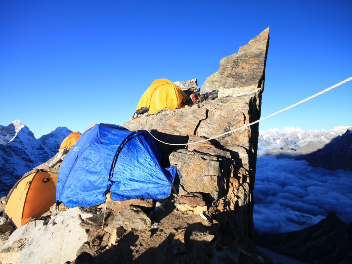 4 camping tents near a cliff of the Himalayan Mountains
