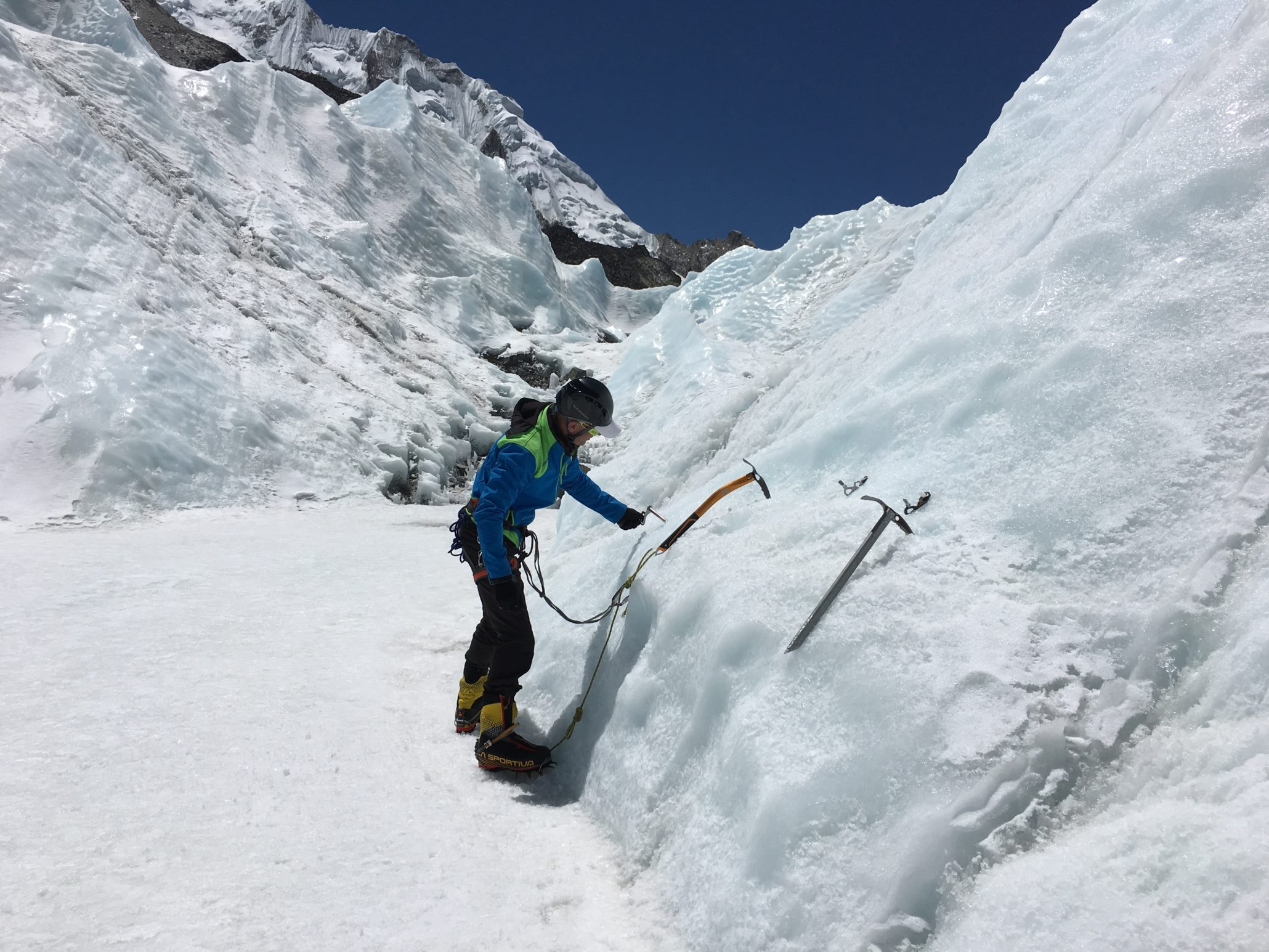 himalayan trekker ice climbing in mountain covered with snow