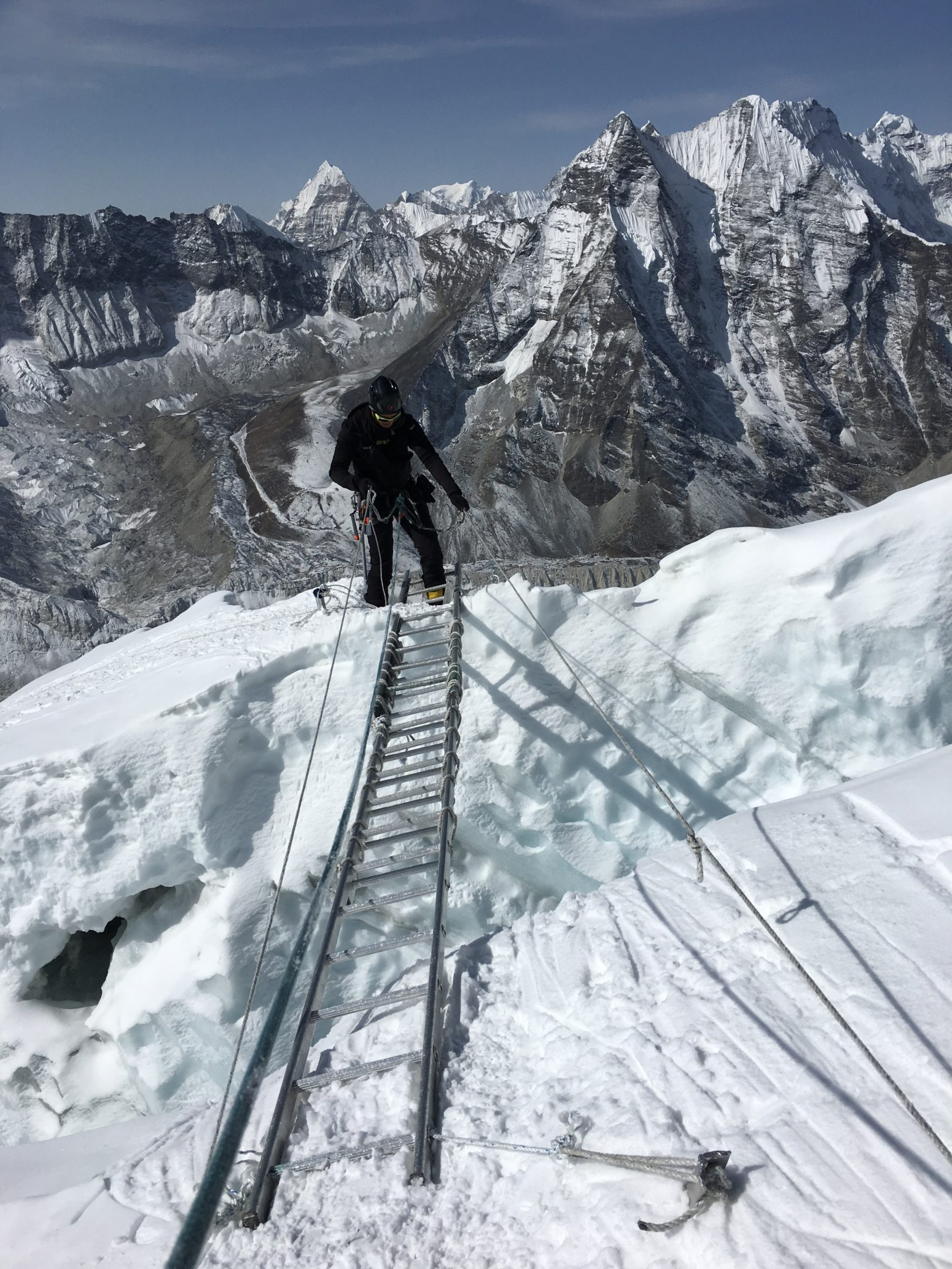 himalayan trekker crossing icefall with ladder in himalayas