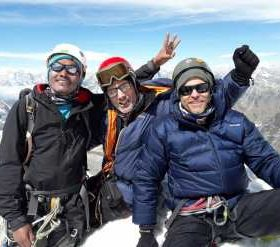 3 Sherpa guides on the peak of Himalaya mountain